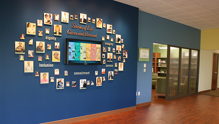 """The """"Stories of Life: Given and Received"""" wall greets visitors and maximizes content in the 400 sq. ft. main lobby."""