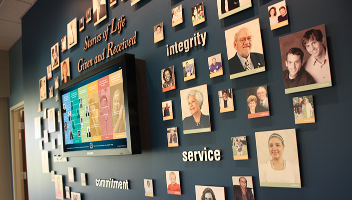 """Portraits of donors and recipients surround the """"Stories of Life"""" interactive display featuring 11 unique stories."""