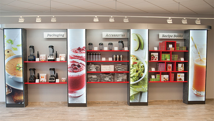 A custom Vitamix red shelving unit holds 20 feet of product separated by storage areas concealed by backlit graphics.