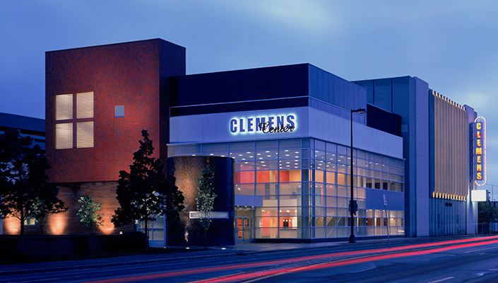 The illuminated exterior signage is located over the main entrance and two-story glass lobby. The   vertical sign at the far end of the building is  parallel to the roadway.