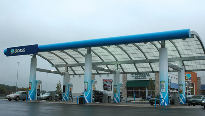 The gas canopy has an illluminated sign box and visual branding elements appearing on the vertical columns that are aligned with the fuel dispensers.