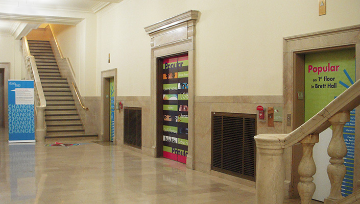 Main Building: lower level greets patrons with vinyl door and elevator graphics emphasizing the Popular collection and its new location.