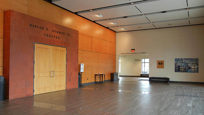 The entrance to the Harlan E. Hummer Theatre and the Disanto-Burke Lobby signage is shown. The plaque honoring the two men is on the same wall as the lobby signage.