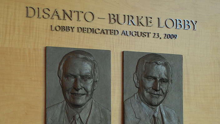 Close-up of the Disanto-Burke plaque with the bas-relief bronze portraits of the two alumni.