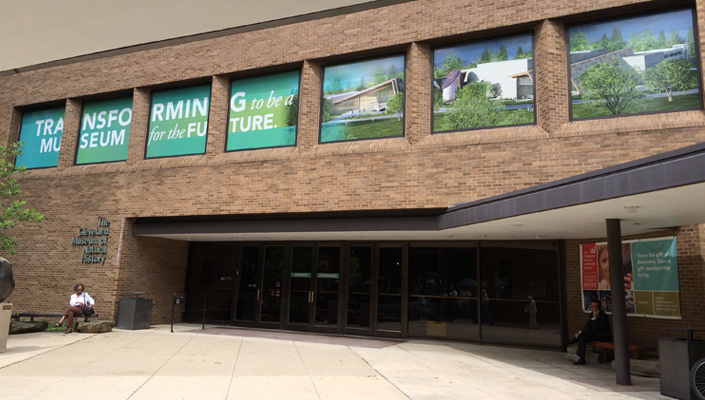 Vinyl window graphics above the main entrance feature an architectural rendering of the future museum.